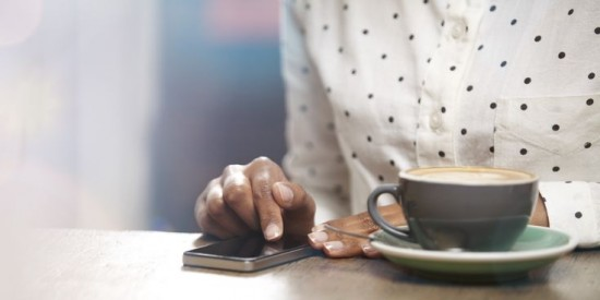 hands with smartphone and cup of coffee
