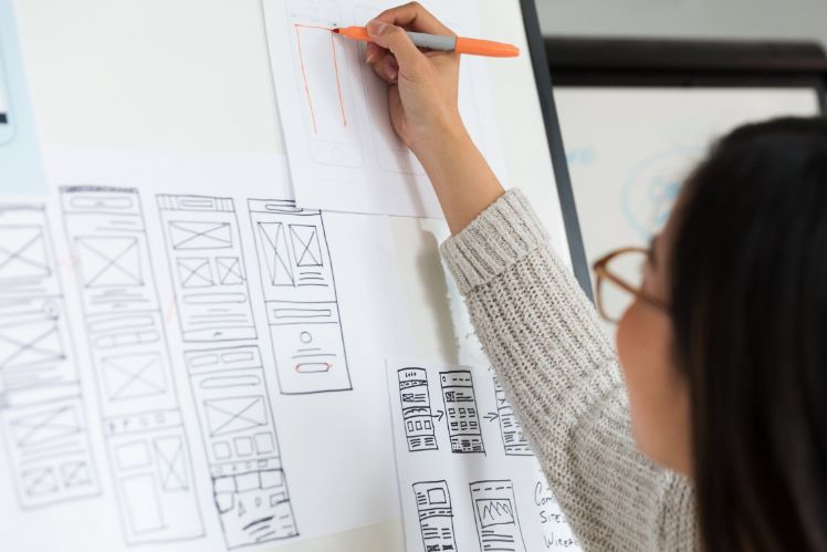 girl drawing app wireframes on a whiteboard