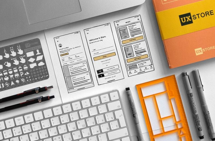 app wireframe sketches and office items laying on a desk