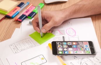 a men hand writing on a green sticker and his smartphone and colorful markers on the table