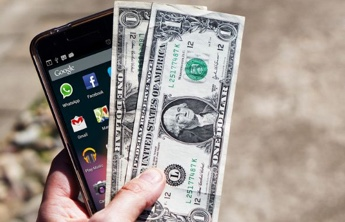 a hand holding a smartphone and 2 banknotes
