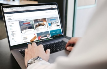 man using a laptop and navigating on a website